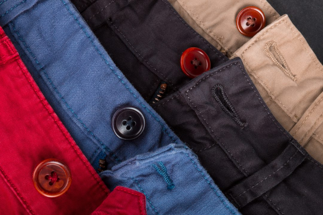 Fragment of four cotton twill pants red, blue, black, beige with open buttons. Close up.
